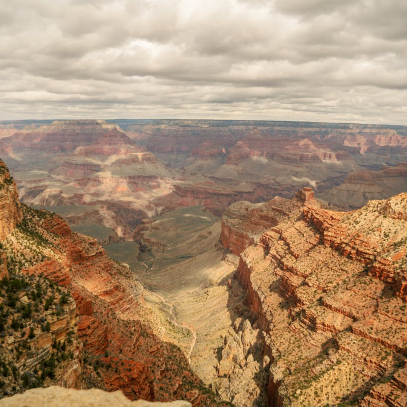 View looking out over the South Rim of Grand Canyon with lots of layered red rock and cloudy skies