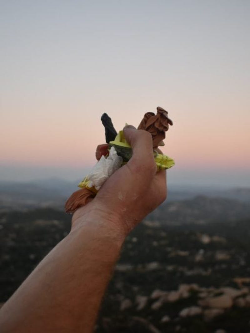 Hand holding trash in front of sunset over mountain range