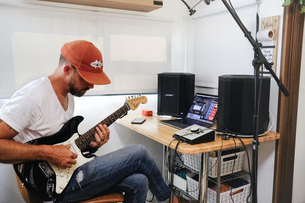 Amick Cutler plays guitar by a desk in an RV.