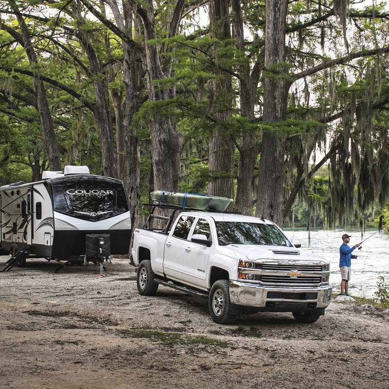 Robert Field fishes as the bank of a river next to his Cougar Travel Trailer and truck.