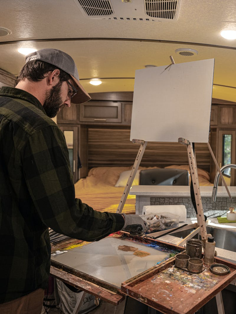 Todd Schabel painting a landscape inside his Crossroads Sunset Trail RV.