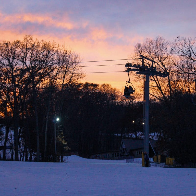 Cascade Mountain ski lift, chair with skiers and a sunset