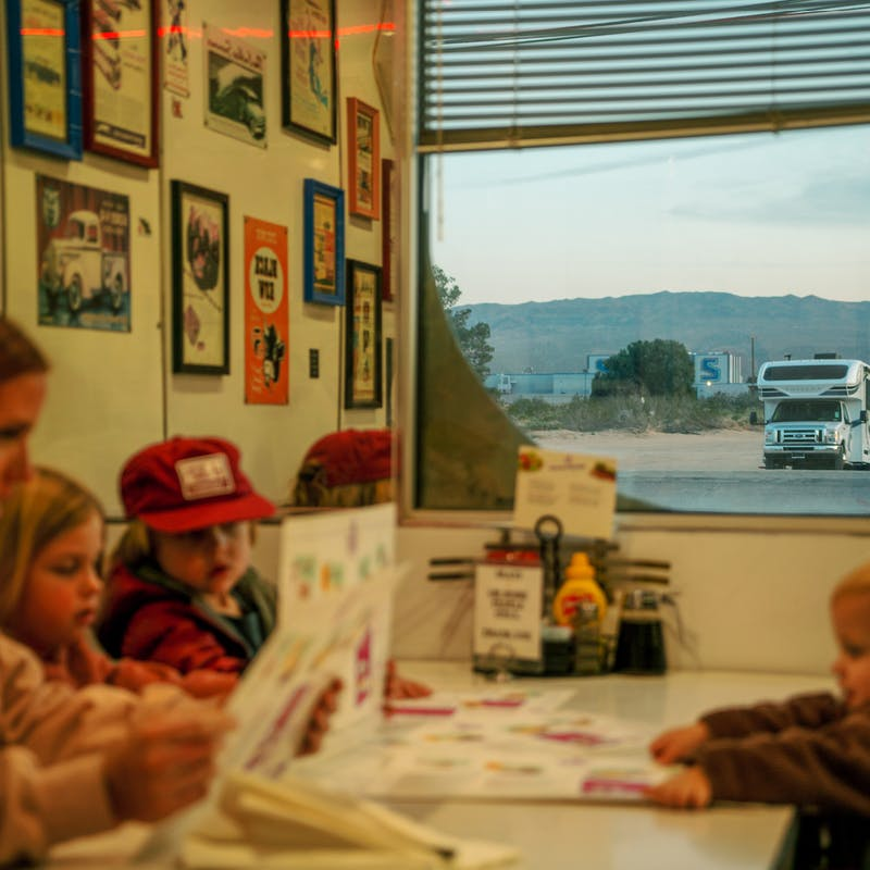Mom sits at a diner table with three young kids reading menus while class c motorhome sits outside window
