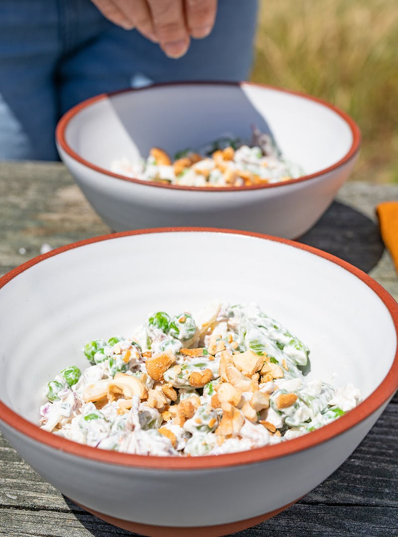 Two white bowls, with hand sprinkling chopped cashews on pea salad.