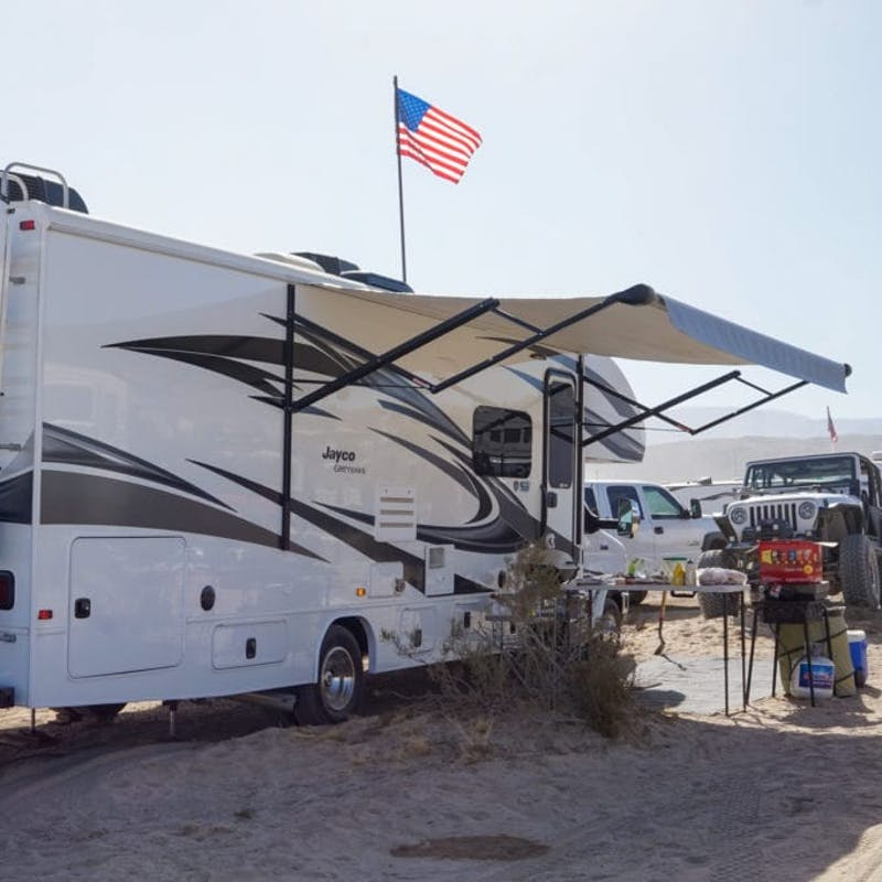 A Jayco RV parked with an American flag in the wind.
