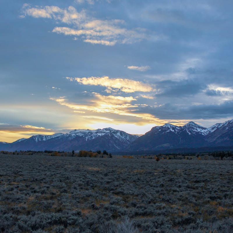 Snowy peaked mountains with grassy field and sunset sky