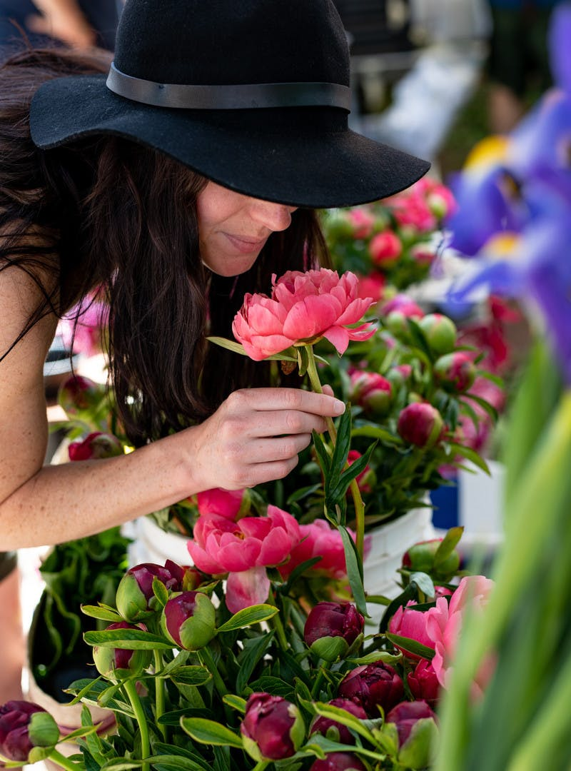 Aubrey in a floppy black hat stops to smell pink and purple flowers.