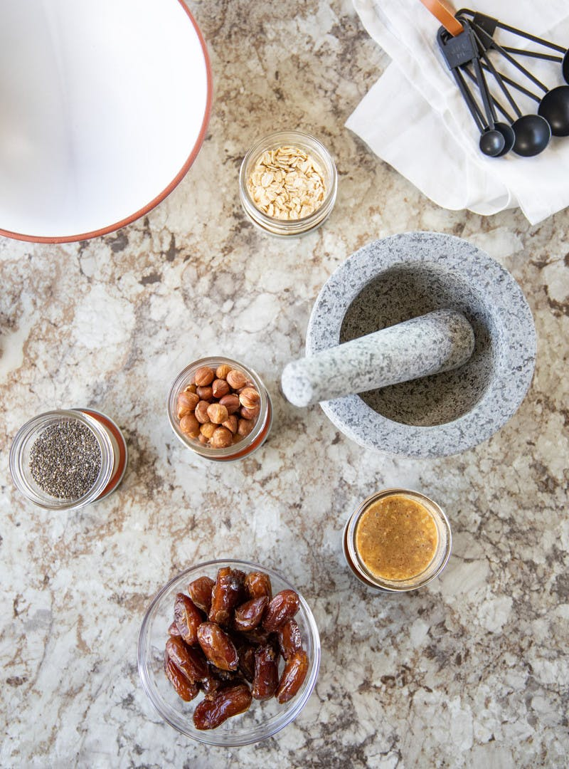 Various bowls and jars on a granite countertop, includes dates, chia seeds, hazelnuts, oats and nut butter.