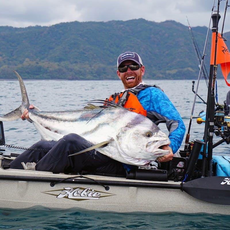 Fisherman sits in kayak with big smile, holding large white fish