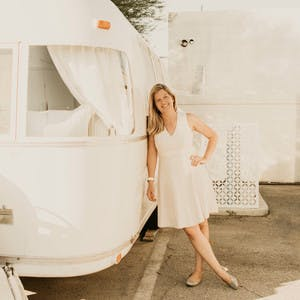 Kristiana Spaulding, in a cream-colored dress and flats, leaning against her Airstream RV in a parking lot, smiling at the camera.
