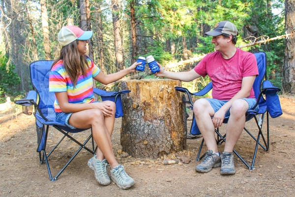 Jesse & Rachael Lyons sitting in camp chairs and cheers each other with drinks in their hands.
