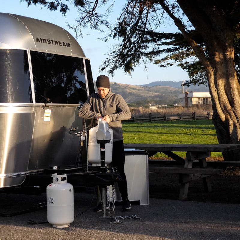 A man standing outside next to his RV holding a propane tank.