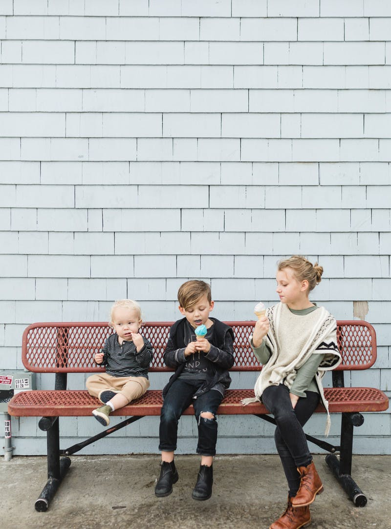 Three kids sit on a red bench eating ice cream cones.