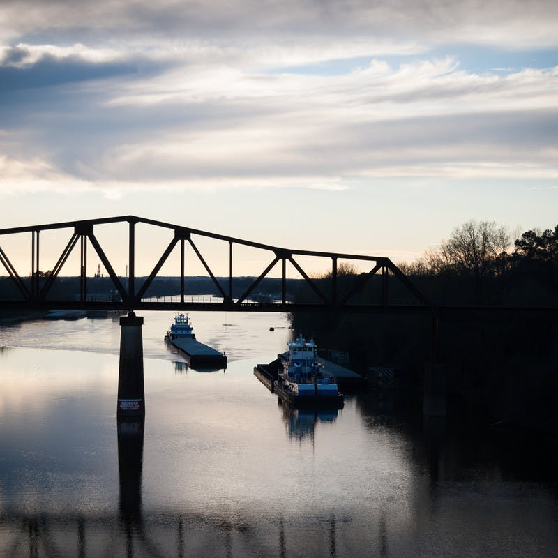 Riverwalk near University of Alabama in Tuscaloosa, Alabama, at sunset with a bridge and boats on the water.