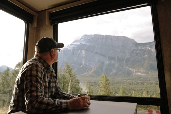 Craig Klinefelter enjoying a cup of coffee as he looks out the window at the mountains of Banff.