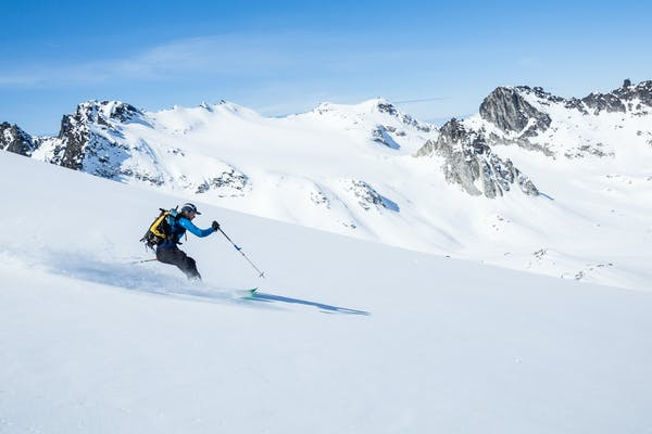 Man with yellow backpack skis down snowy mountain with jagged mountain peaks in the background