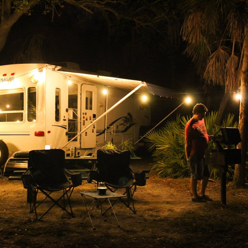 Jesse & Rachael Lyons' cook at a grill at their campsite in front of their Keystone Cougar RV.