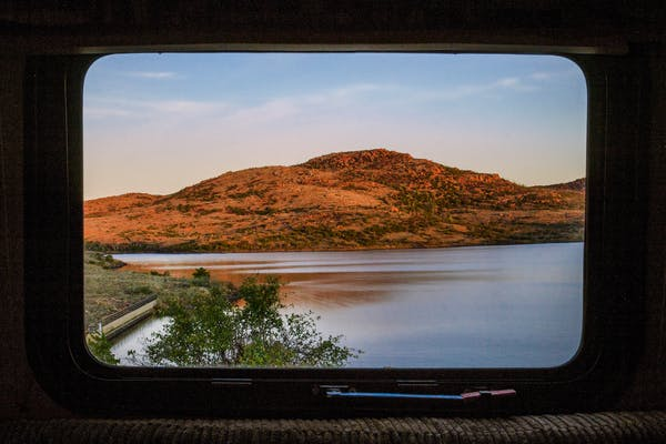 A view out an RV window of a russet hill on the coast of Lake Jed Johnson in Oklahoma.