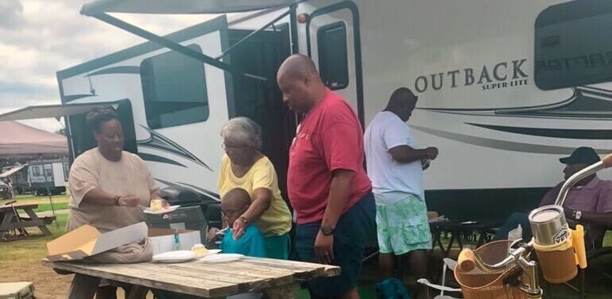 A family sets a picnic table outside of their RV.