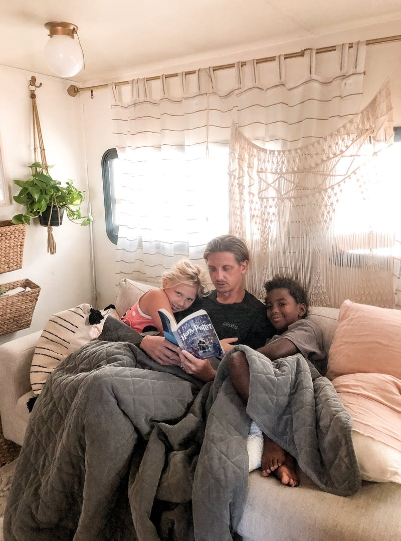 Shannon Carew's children read a book with her husband as they sit inside their Highland Ridge RV.