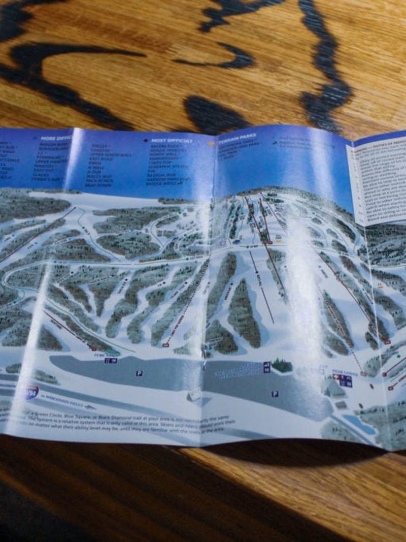 Map of Cascade Mountain Ski Resort, with all runs and lifts, on wooden surface
