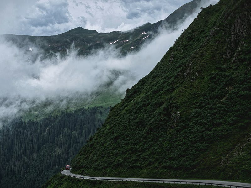 Class B Camper Van driving through the mountains on a windy road, low clouds with dark green cliffs