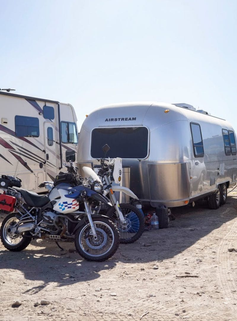 An Airstream and a couple of dirt bikes.