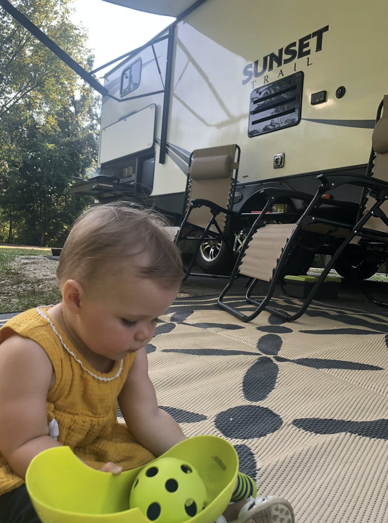 A baby playing on the ground outside an RV.