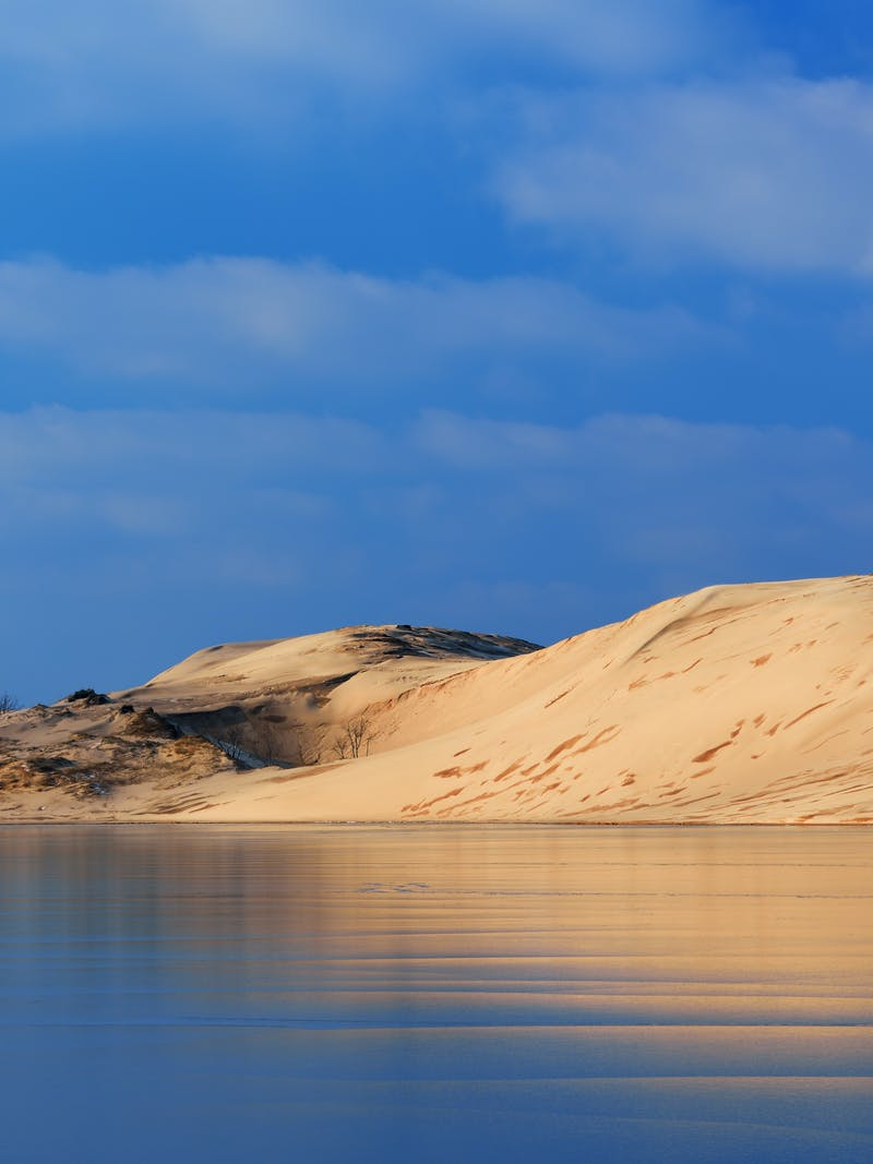 A sand dune reflects in a nearby lake.