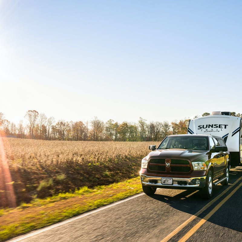 Todd & Marcia Schabel driving their Crossroads Sunset Travel Trailer down a road next to a field of crops.