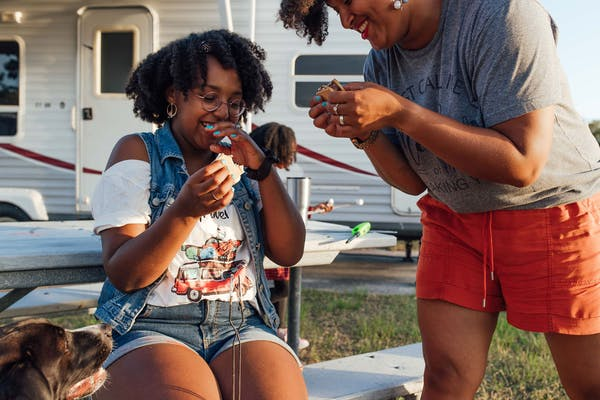 Mom and daughter laughing while eating s'mores.