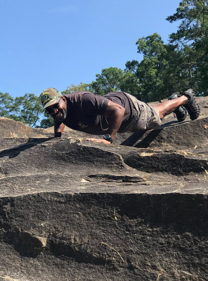 Mack Womack doing a pushup while on a hike.