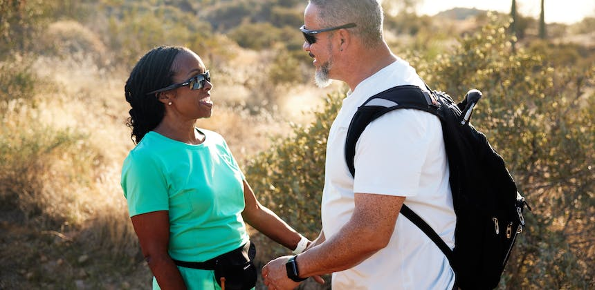 Robin and Warren smile at each other while on a hike.