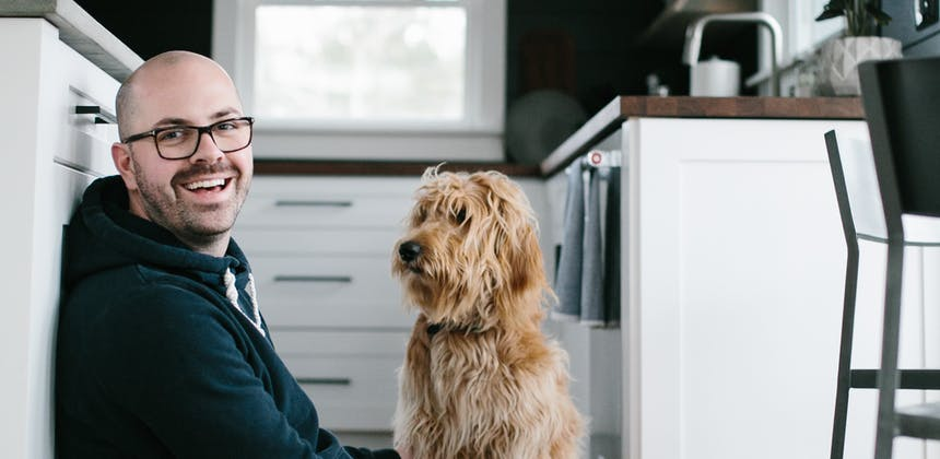 Jeff Shipley and his dog Andie sitting together on the floor of a kitchen.