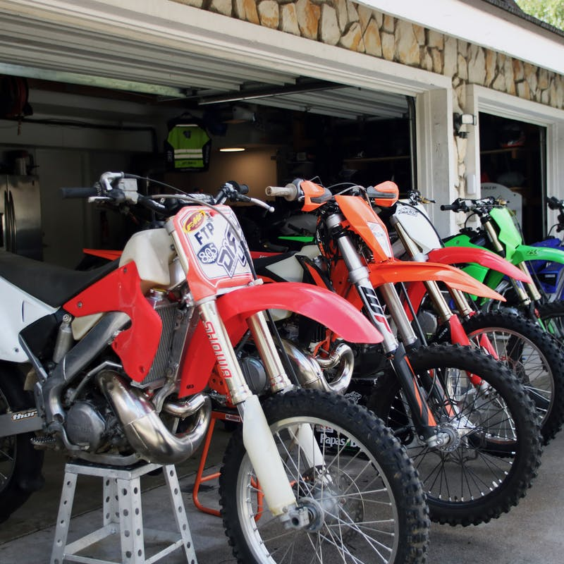 Dirt bikes raised up on blocks to tune them up before a trip.