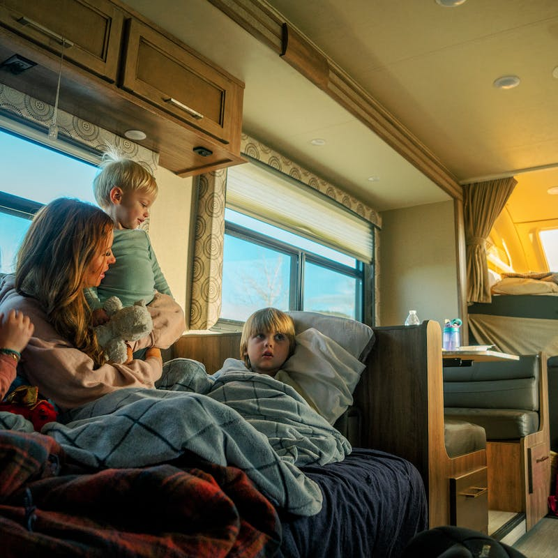 Mother snuggles with three kids inside RV on couch