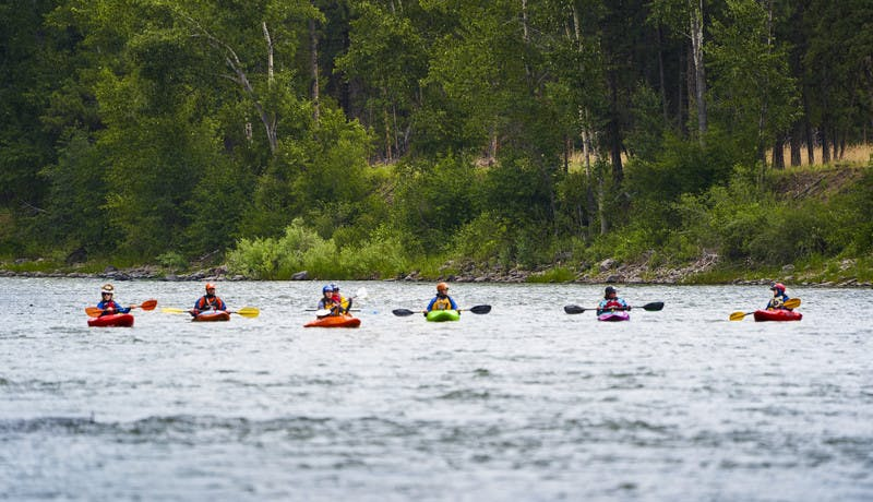 A wide shot of the participants kayaking in the Blackfoot River.