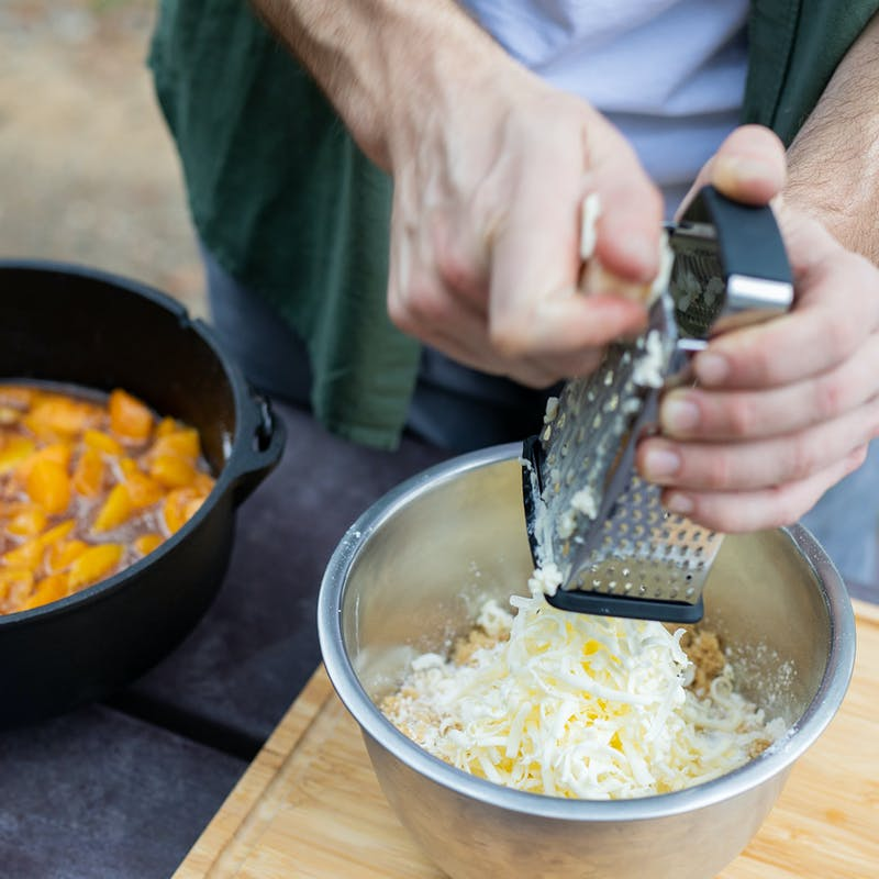 Grating cold butter into a bowl for the cobbler topping.