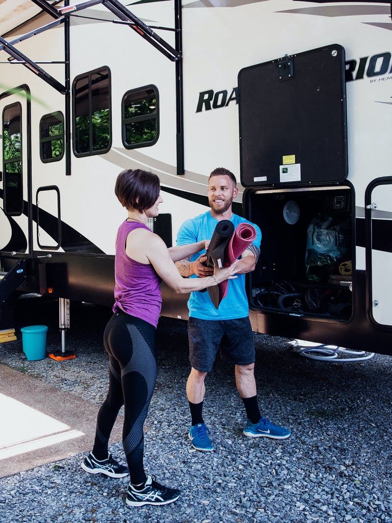 A man handing woman two yoga mats he retrieved from an RV's exterior storage cubby.