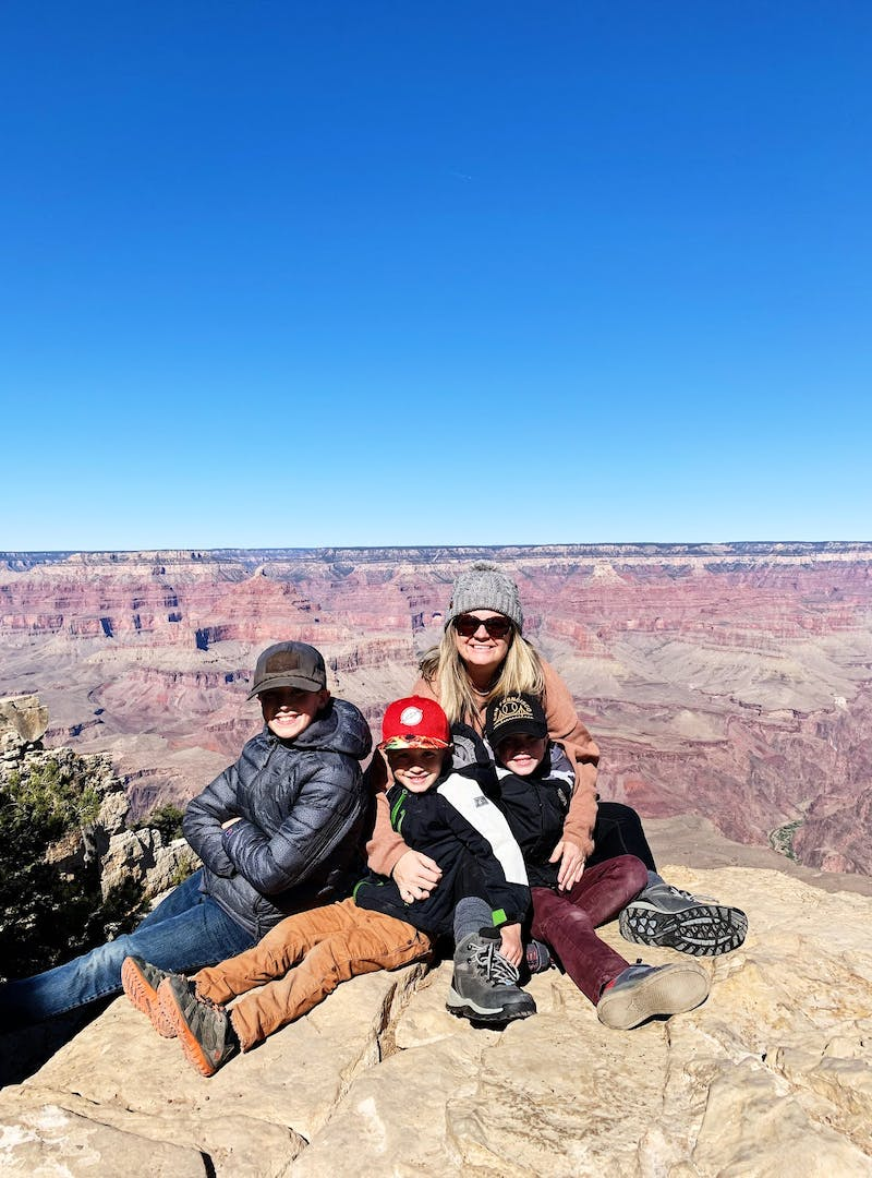A mom and three boys posed for a picture  in front of the Grand Canyon.