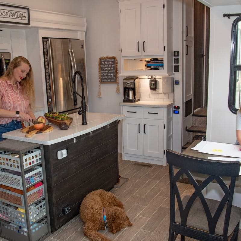 Jama Maples chops food in the kitchen of her Keystone RV while her daughter colors at the kitchen table.