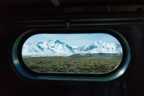 Snowy mountain peaks in the distance, seen through an oblong, rounded RV window.