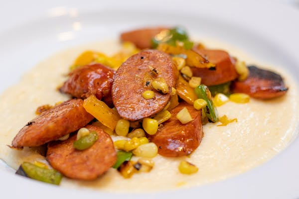Sausage, corn and cooked peppers over creamy grits.