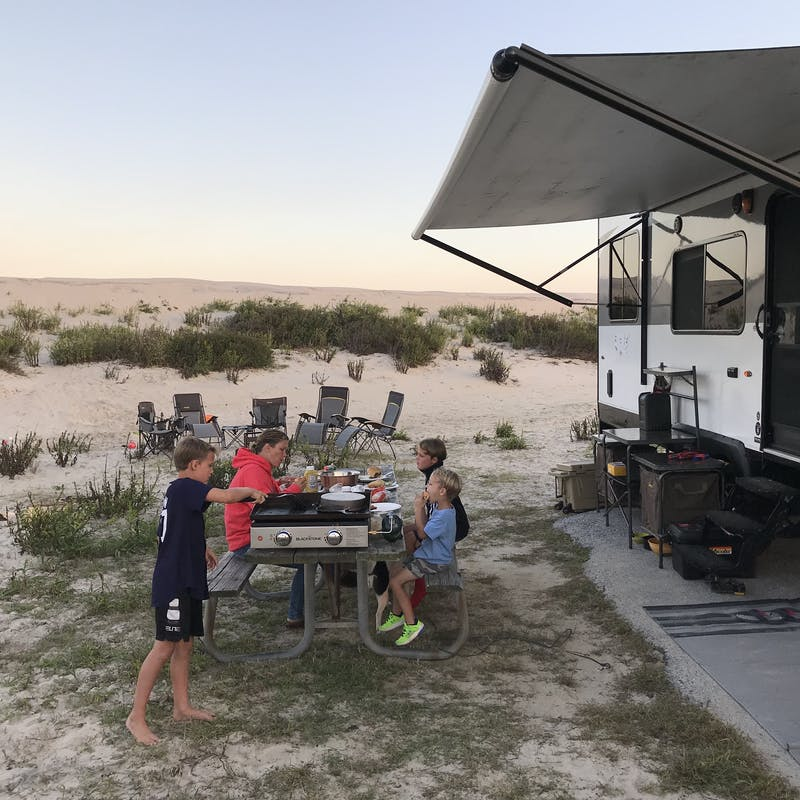 Kids at a picnic table outside an RV.
