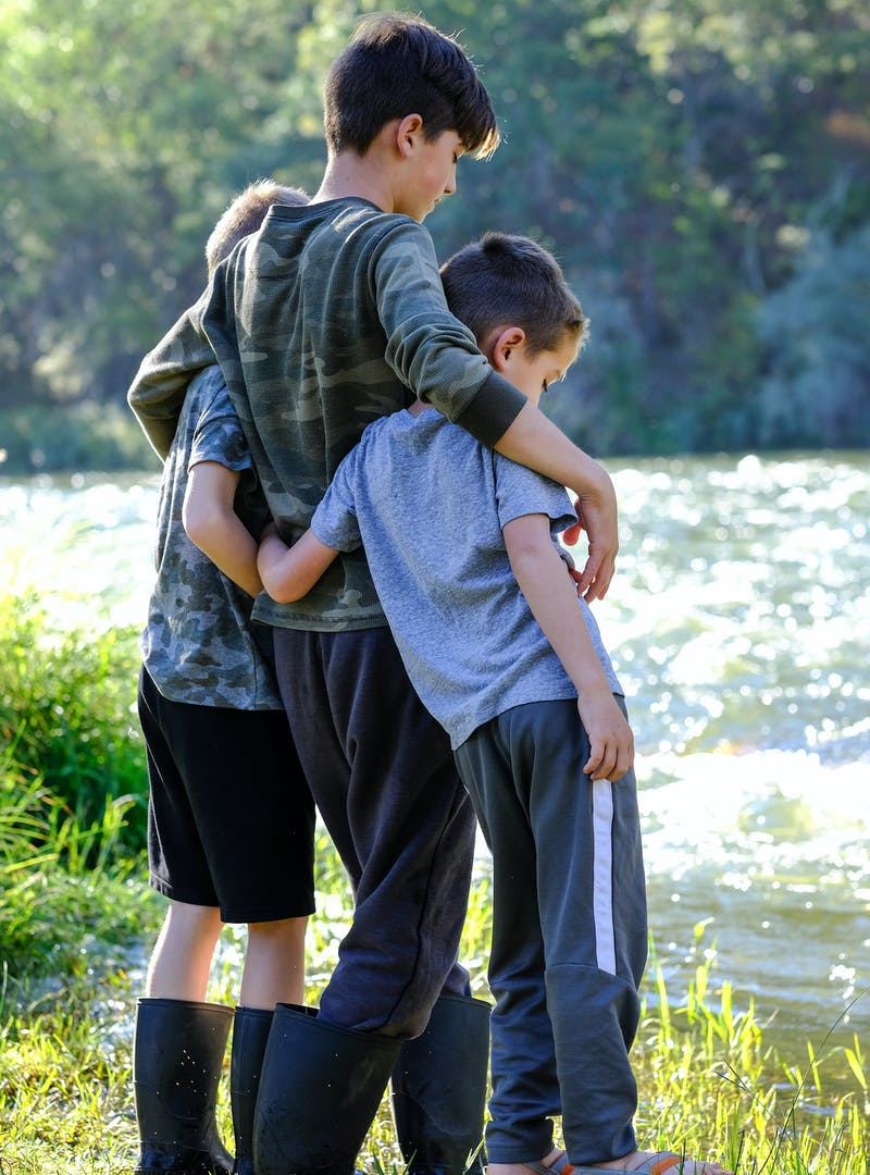 Three young boys stand arm in arm by a river.