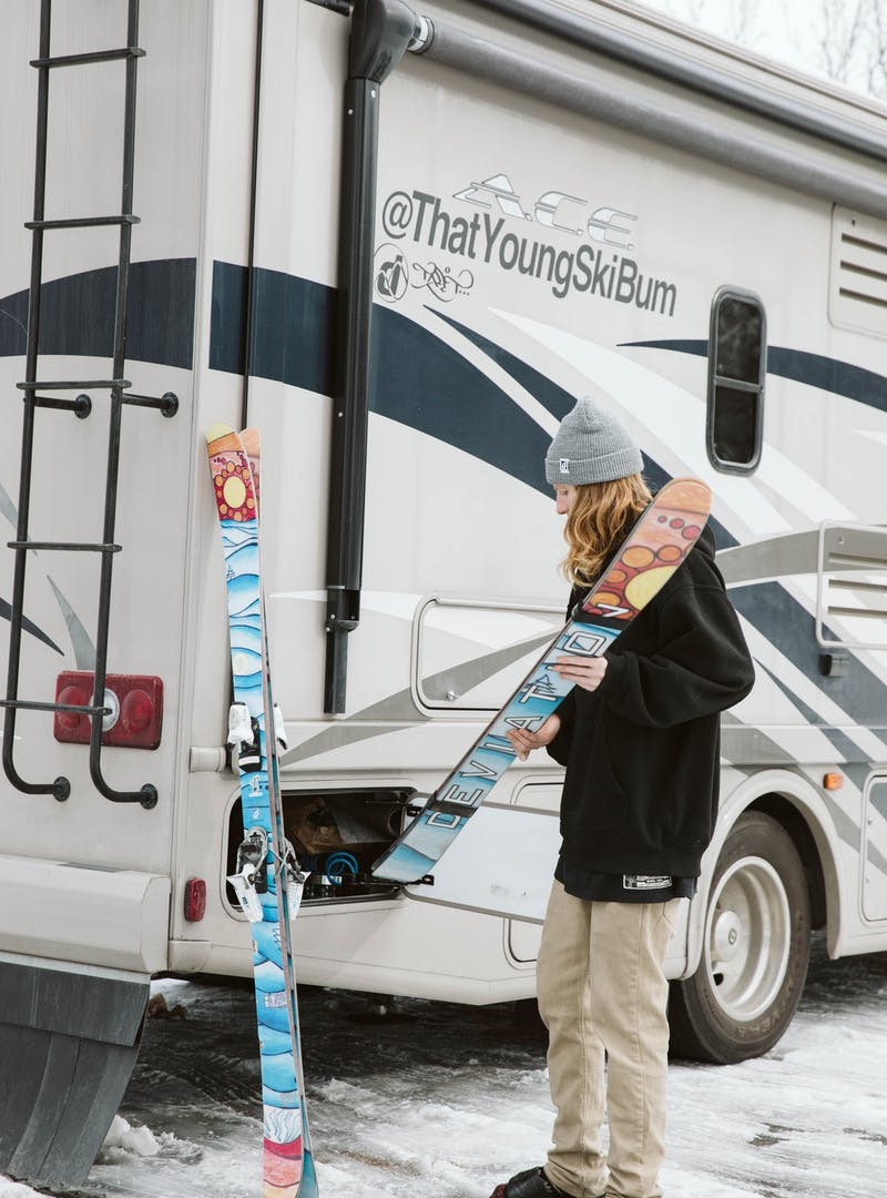 Packing skis into outside cubbies in an RV.