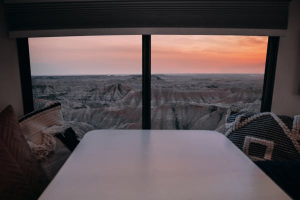 A sunset view out an RV window, facing the landscape of Badlands National Park.