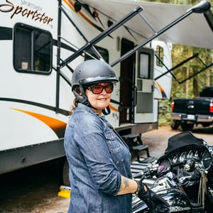 A woman smiles as she sits idle on her motorcycle in front of her toy hauler RV.