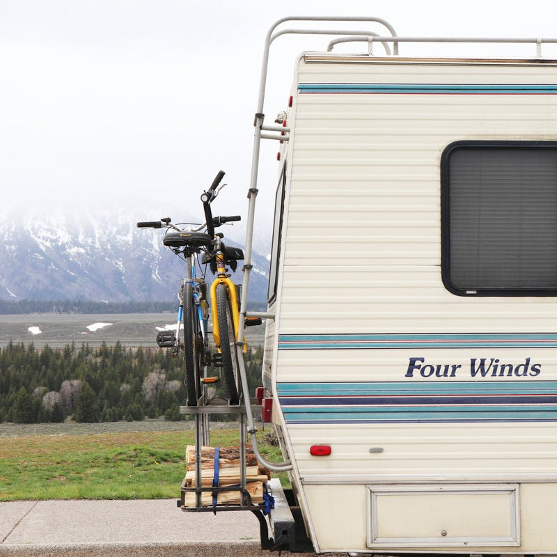 Back of Class C Four Winds motorhome, with two bikes and some firewood strapped to the back, and snowy mountains in the background.