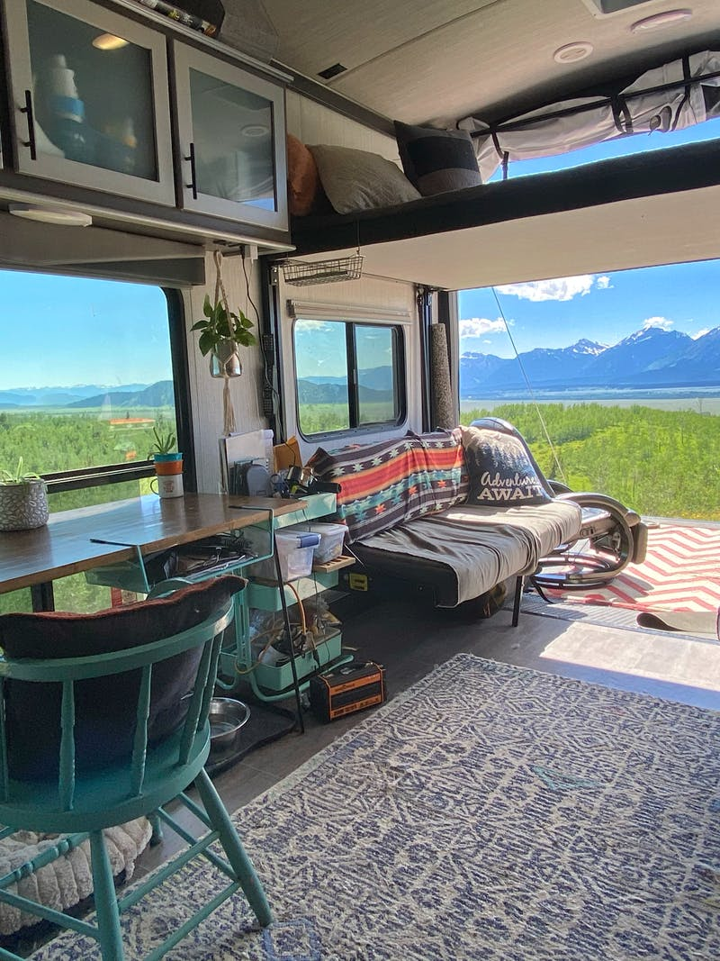 Amy Rekart's Cruiser Stryker toy hauler's back patio opens up to a beautiful mountain scene with lush grass and sunny skies.